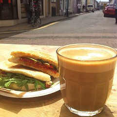 Having a sandwich and a flat white in the sun