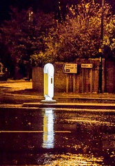 Day 256, 2016, a photo a day. (lizzieisdizzy) Tags: howiemarsh night nighttime dark wet rain raining acle norfolk highstreet reflections trees leaves tarmac pavement puddles wall brick sign signposts plinth bollard illuminated puddle splash