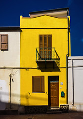 Yellow house (aistora) Tags: house street facade elevation narrow small balcony window door wood wall entrance pavement roof sky skyline color colour colourful yellow blue vivid vibrant bright sunny sunlight sunshine mediterranean ink indigo deep conrast combo combination harmony complementary light shadow shadows graphic poster postcard sony alpha ilce 6000 lightroom island sardinia village portoscuso town port south southern holiday vacation tourism tourist kit zoom lens 1650mm epz1650oss