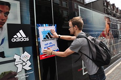 Protester sticks a poster on the Adidas shop windows (War on Want) Tags: london shop protest olympics adidas sweatshops workersrights
