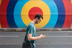 Oxford Street, London (jaumescar) Tags: street spot color man guy phone walking smartphone bag wall advert red yellow blue tshirt urban city london road candid funny head arm