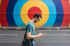 Oxford Street, London (jaumescar) Tags: street spot color man guy phone walking smartphone bag wall advert red yellow blue tshirt urban city london road candid funny head arm