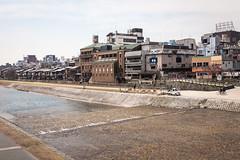 kyoto-2745 (yukkycakes) Tags: kyoto japan kamogawa kamoriver water river cobblestones buildings restaurants trees bikes bicycles truck
