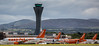 easyJet aircraft at Edinburgh Airport seen against a background of the airport's 57m/187 foot high control tower and the Pentland Hills.