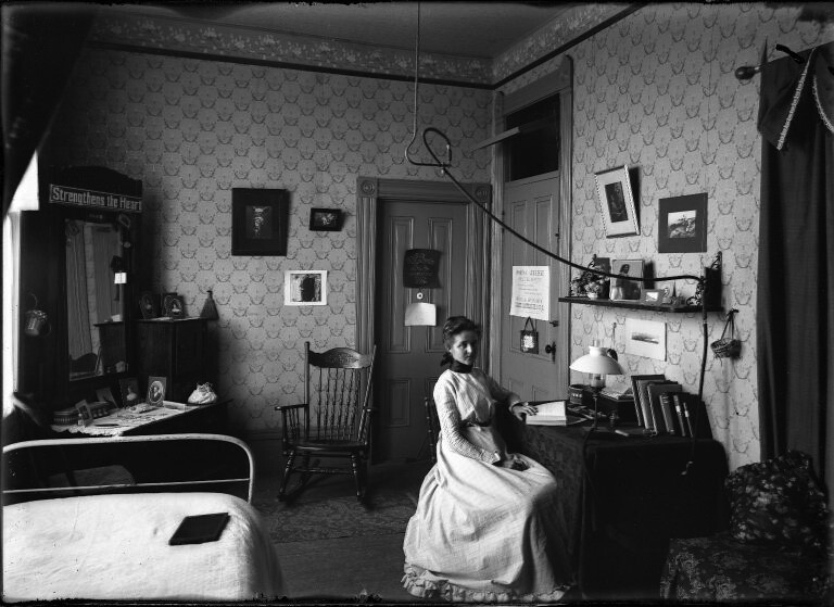 ... Pomona College student Edith Parker 1903 sits at a desk in her room in  Sumner Hall
