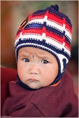 Performance Anxiety! (ZeePack) Tags: baby child infant ladakh leh festival innocent frowning cap red woolens jammukashmir india canon 5dmarkii milestoneenterprisein milestoneenterprise