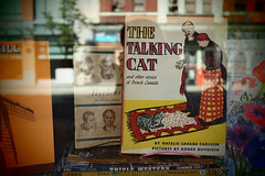 """The Talking Cat"" (Eric Flexyourhead) Tags: vancouver canada britishcolumbia bc downtown westpender penderstreet city urban detail fragment bookshop bookstore thepaperhound window glass reflections display books thetalkingcat artfilter pinhole vignette olympusep1 panasoniclumix20mmf17"