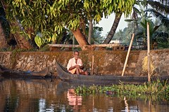 A Gracious Man Poses (The Spirit of the World) Tags: local man canoe kerala backwaters southernindia india morning locallife dailylife water reflections trees palmtrees