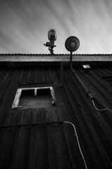 Up (- David Olsson -) Tags: old longexposure roof summer blackandwhite bw house building window monochrome mono wooden nikon sweden tripod sigma august spotlight lookingup cables le wires worn lamps grayscale 1020mm 1020 2012 dx värmland ndfilter grums skymotion slottsbron d5000 cloudmotion davidolsson nd500 lightcraftworkshop
