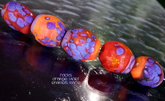 Rocks Orange Violet Enamels (Laura Blanck Openstudio) Tags: openstudio openstudiobeads glass handmade lampwork beads bead set jewerly murano big fine arts artist artisan show festival wearable pebbles stones rocks nuggets faceted transparent whimsical funky odd colorful multicolor organic earthy abstract asymmetric frit speckles made usa published winner category south miami orange yellow coral matte glow frosted etched opaque enamel enameled bright happy violet purple lilac lavender grape maize tropical carrot warm