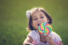 (Rebecca812) Tags: family portrait food girl smile grass childhood outdoors happy kid colorful child candy sweet innocent daughter eat hazeleyes treat enjoyment indulge brownhair fiveyears rainbowcolors hairbow canon5dmarkii rebecca812