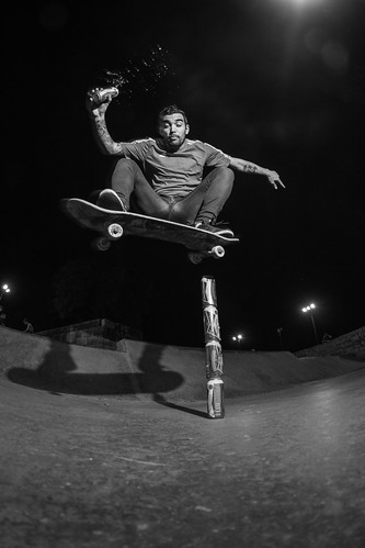 Skateboard in black and white jumping beer cans, with another in his hand.