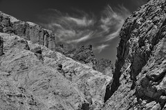 Walking in Golden Canyon and Taking in the Views (Black & White, Death Valley National Park) (thor_mark ) Tags: amaragosarange blackwhite blueskies blueskieswithclouds capturenx2edited cliffwalls cliffface cliffs cloudwisps colorefexpro day3 deathvalleynationalpark desertlandscape goldencanyontrail greatbasinranges hillsides lookingne nature nikond800e portfolio project365 silverefexpro2 triptodeathvalleyandcalifornia westgreatbasinranges furnacecreek california unitedstates
