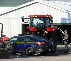 NY State Trooper Washing A Tractor. (dccradio) Tags: malone ny newyork franklincounty northernny upstateny countyfair franklincountyfair fairgrounds fun entertainment communityevent festival nystatetrooper policecar building washing tractor caseih tractorcab police policeman kubota ag agriculture agricultural ford hose water spray