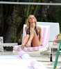 Victoria's Secret Angel, Erin Heatherton, shows off her best sexy poses in a pretty floral bikini during a photo shoot poolside. Miami Beach, Florida
