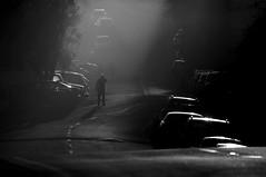 Transported 2 (blueteeth) Tags: figure road shaftofsunlight monochrome blackandwhite highkey roadmarkings parkedcars silhouettes