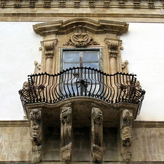 A window and wrought-iron balcony, Palazzo Beneventano, Scicli, Sicily (Hunky Punk) Tags: baroque sicilian scicli sicily italy sicilia italia palazzo beneventano window balcony wroughtiron stonework stone carving carved grotesque face figure woman girl barocco siciliano