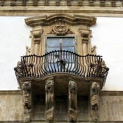 A window and wrought-iron balcony, Palazzo Beneventano, Scicli, Sicily (Spencer Means) Tags: baroque sicilian scicli sicily italy sicilia italia palazzo beneventano window balcony wroughtiron stonework stone carving carved grotesque face figure woman girl barocco siciliano balcón balkon dwwg
