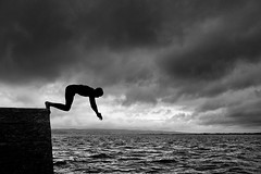 full-tide (zip po) Tags: sea summer blackandwhite silhouette clouds mono pier swimmer diver ballinacourty