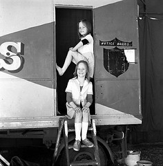 Twins..circus act (Don Jackson) Tags: life girls portrait people bw cute art strange smile closeup female pose square amazing twins legs circus profile steps young relaxing thoughtful photojournalism documentary surreal atmosphere social doorway mysterious karma unusual caravan gesture sureal journalism global