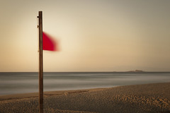 Bathing Prohibited (Bernd Schunack) Tags: ocean sardegna italien light sunset red sea storm motion blur rot beach island lumix fantastic movement long exposure mediterranean italia sardinia sonnenuntergang empty flag corsica shoreline stormy pole insel filter shore nd flagpole bathing minimalism waving baden fahne sardinien prohibited verboten fluttering rote korsika mittelmeer castelsardo badesi fahnenmast gx1 poltu biancu wehende