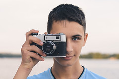 Teenager with vintage rangefinder camera. (Blackcatstudio) Tags: casual person young boy photographer camera teenager photo photograph happy cheerful hobby guy man cool portrait people lifestyle fun caucasian digital photographic one face male model joyful smiling old vintage child little color kid summer nikon d7000