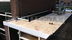 Dakdekker: Na het timmerwerk is het tijd voor de aanleg van een meerlaagse bitumineuze dakbedekking. Eerste schroeflaag van APP gemodificeerde, éénzijdig gebitumineerde polyestermat 460 P60 dakbedekking