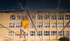 Marching on Water (marcin baran) Tags: color colour girl kid child walk walking play playful pov perspective reflect reflection puddle water windows building fuji fujifilm x100 x100t fujix100 human element factor gliwice poland polska marcinbaran city urban street streetphotography streetphoto