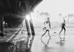 Rushing to the surf  (pixelmama) Tags: ocean california sea blackandwhite bw beach monochrome shadows running palmtrees pacificocean flare surfers imperialbeach imperialbeachpier thehumanelement chasinglight pixelmama