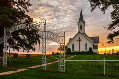 Our Saviors Church (John D. Stocker) Tags: johnstocker paintedspur photography wwwpaintedspurphotographycom church sunrise hdr morning lutheran religion religious christian cross cemetary graves gravestones fence gate beldinville wisconsin wi el paso country rural outdoor summer grass mowed lawn clouds sun sidewalk leading lines steeple 1919 glow saviors