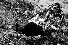 Oh I do like to be beside the seaside ('Ollie') Tags: bw white man black london beach monochrome sunglasses electric thames river grey nice wire chair day deckchair singing guitar stripes sony south tide stripe amp bank pebbles southbank sparkle deck pebble mans sing singer beaches singers microphone daytime sings sparkling tides a500
