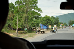Wait... (Roving I) Tags: workers workmen hardhats helmets waiting transportation loads motorbikes trailers trees roads rural langco vietnam