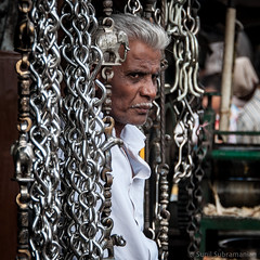 The Chain Man - A trader looks through a screen of metal chains.. (sunil.subramanian) Tags: street old flowers people food india color portraits children buzz happy cow ganesha nikon faces watches tea steel rustic innocent smiles culture dreams gods letterbox sunil chennai tamil hindi babas vessels mgr businessmen subramanian yogis marwadi havenots nikond90 sowcarpet