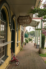 Hogansville Cleaners (jwcjr) Tags: hogansville hogansvillega pentax smalltown smalltownga smalltowngeorgia hogansvillecleaners sidewalk architecture southernarchitecture sign tricycle window usa