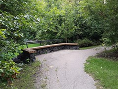 Sedentary seating atop a terraced wall (canadianlookin) Tags: green park kingspark winnipeg manitoba bench tranquility september 2016