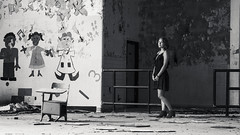 Taking it in (Nate Conn) Tags: people monochrome light dark abandoned building urban decay exploring exploration urbex dress model girl woman teen teenager black white blackandwhite bw gray grayscale heels high big room painting elementary school wide field view aspect ratio desk standing