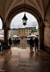 A cubierto (Perurena) Tags: lluvia rain mojado soportales refugio farol lamp gente personas humanos mercadodelospaos cracovia polonia