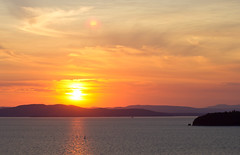 sunburst (porschelinn) Tags: pink blue sunset red orange sun lake reflection nature water beautiful silhouette yellow clouds burlington sailboat canon eos vermont bright dusk adirondacks lakechamplain burlingtonvermont 550d sunburt t2i porschelinn porschebrosseau