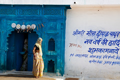 Doorstep, Orchha (Marji Lang Photography) Tags: street door travel blue people woman india white house home colors wall writing walking photography women colorful walk candid indian streetlife streetscene dailylife tradition indien doorstep hindi san
