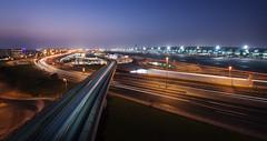 Infrastructure (momentaryawe.com) Tags: longexposure blue train lights evening dubai metro dusk airplanes uae middleeast terminal trail t3 unitedarabemirates d800 dubaiairport dubaimetro catalinmarin momentaryawecom