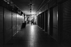 Temporary Monopoly (Andrew Tan 2011) Tags: light blackandwhite bw dark vanishingpoint singapore closed market shops radiate lowkey tiongbahru pointsource matchpointwinner thechallengefactory