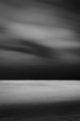 Pacific Clouds (barkingduck99) Tags: ocean california longexposure sky bw copyright white abstract motion black blur art beach nature water monochrome lines misty night clouds contrast stars sand soft glow bare smooth shoreline trails pebbles sensual foam edge dreamy curve minimalistic richardkownacki