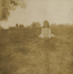 Little girl in a graveyard, circa 1900 (liquidnight) Tags: old blackandwhite bw white cute girl monochrome cemetery graveyard childhood sepia vintage hair children found photo kid alone sitting child dress antique young headstones curls eerie creepy collection sombre photograph mementomori vernacular ribbon melancholy tombstones seated sullen 1900s foundphotos ringlets