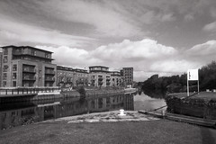 View towards Leeds (Saturated Imagery) Tags: blackandwhite slr film monochrome 35mm river canal apartments lock yorkshire leeds riveraire microphen aireandcaldernavigation luckyshd100 luckyshd vivitar28mmf25 ilfordmicrophen prakticatl5b film:iso=100 developer:brand=ilford developer:name=ilfordmicrophen film:brand=lucky film:name=luckyshd100 knowesthorpe knostrup filmdev:recipe=8021