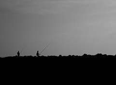 Fishermen (seanjonesfoto) Tags: ocean africa travel sea vacation portrait sky people blackandwhite food beach silhouette d50 relax 50mm fishing fisherman nikon morocco seafood poles nikkor oualidia