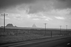 The road past Shiprock (Jodie Dobson (Moving Country) is that busy?) Tags: shiprock southwest usa america americana southwestroadtrip roadtrip powerlines bw blackwhite newmexico rocks road lines canon canon6d 6d fullframe fullframedslr countryside sky