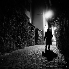 nouvelle vague (Emiliano Grusovin) Tags: street city shadow blackandwhite bw hat silhouette night alley strada mood sony ombra highcontrast evil bn pancake alpha cinematic 16mm f28 notte biancoenero cappello filmnoir città altocontrasto mirrorless nex3