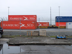 Intermodal Yard, SODO, Seattle (Blinking Charlie) Tags: seattle usa harbor waterfront overcast container barbedwire chainlinkfence washingtonstate pallets bnsf skids sodo 2012 floodlights hamburgsüd cofc containercranes brokenpavement doublestacktrain intermodalyard curbcutout blinkingcharlie fujifilmx10 utahavenues seattleinternationalgatewaynorth graydrearysky