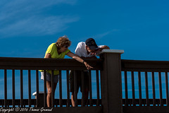 Down There! (Thomas Gremaud) Tags: couple blue pointing clearwater sky seashore pier