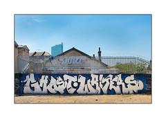 Graffiti (Ghost Writers), East London, England. (Joseph O'Malley64) Tags: ghostwriterscrew graffiti streetart eastlondon eastend london england uk britain british greatbritain wall walls wallmural mural muralists brickwork pionting securityfencing securityspikes meshfencincpanel razorwire victorianbuilding chimneypots chimneys buddleia tower officeblock housing estate openground dangerantiintruderdevices aerosol cans spray paint